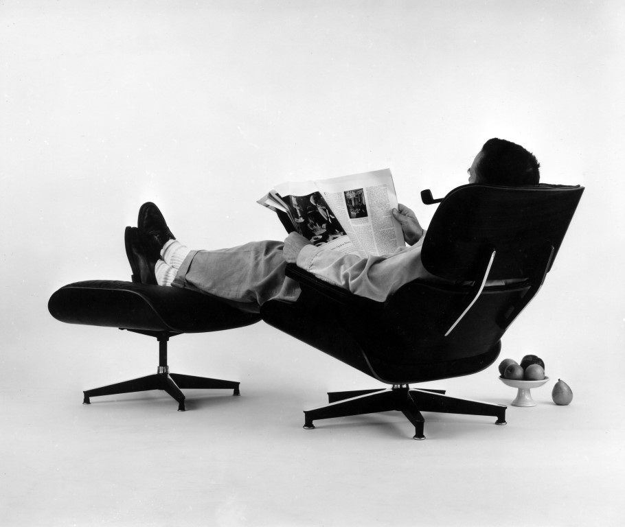 Charles Eames in the plywood Lounge and Ottoman 1956. Eames Office LLC.