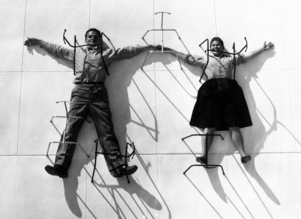 Charles and Ray Eames posing with chair bases ® Eames Office LLC
