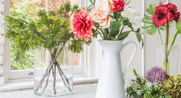 artificial flowers in jug and vase