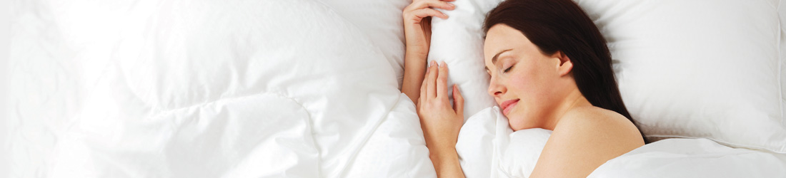 woman sleeping in bed with white bed linen
