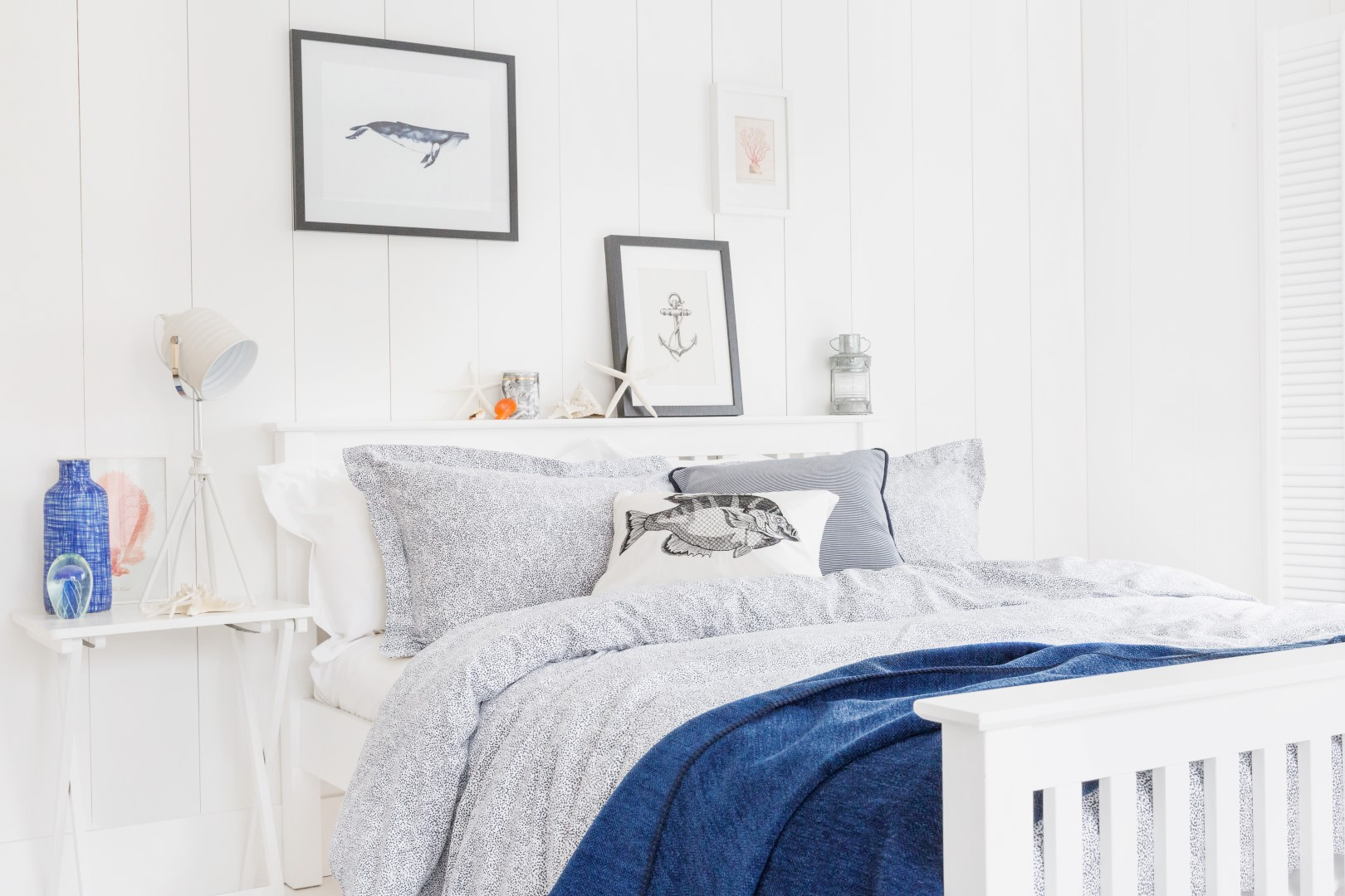 White bedroom with printed blue bed linen and coastal accessories