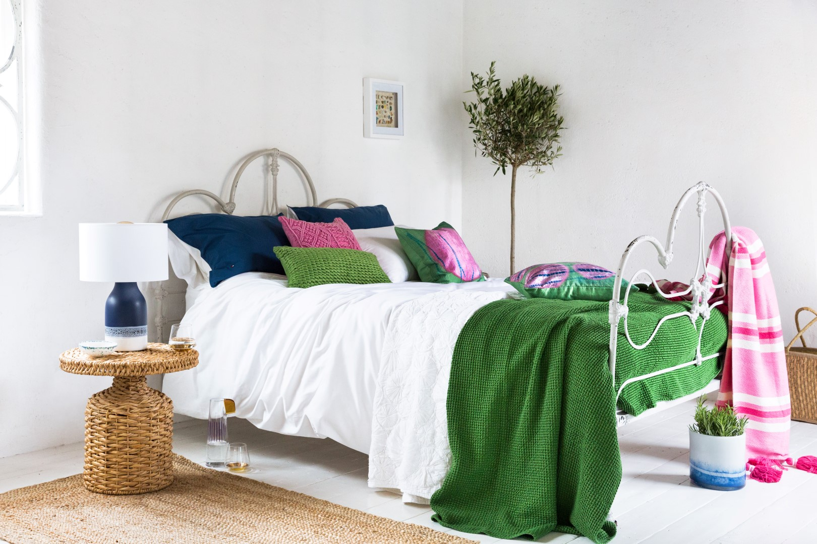 White bedroom with green throw and blue and pink cushions
