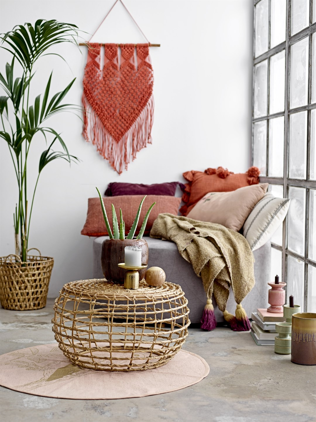 White room with red wall hanging and rattan table