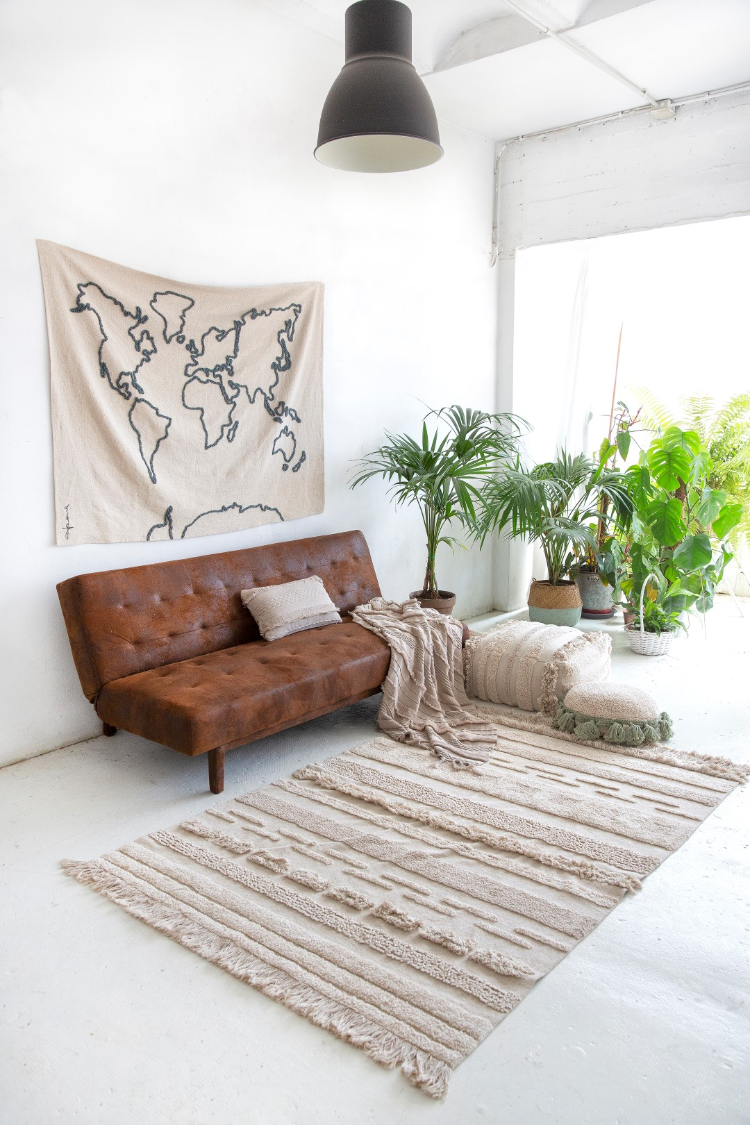 White room with leather sofa and textured rug