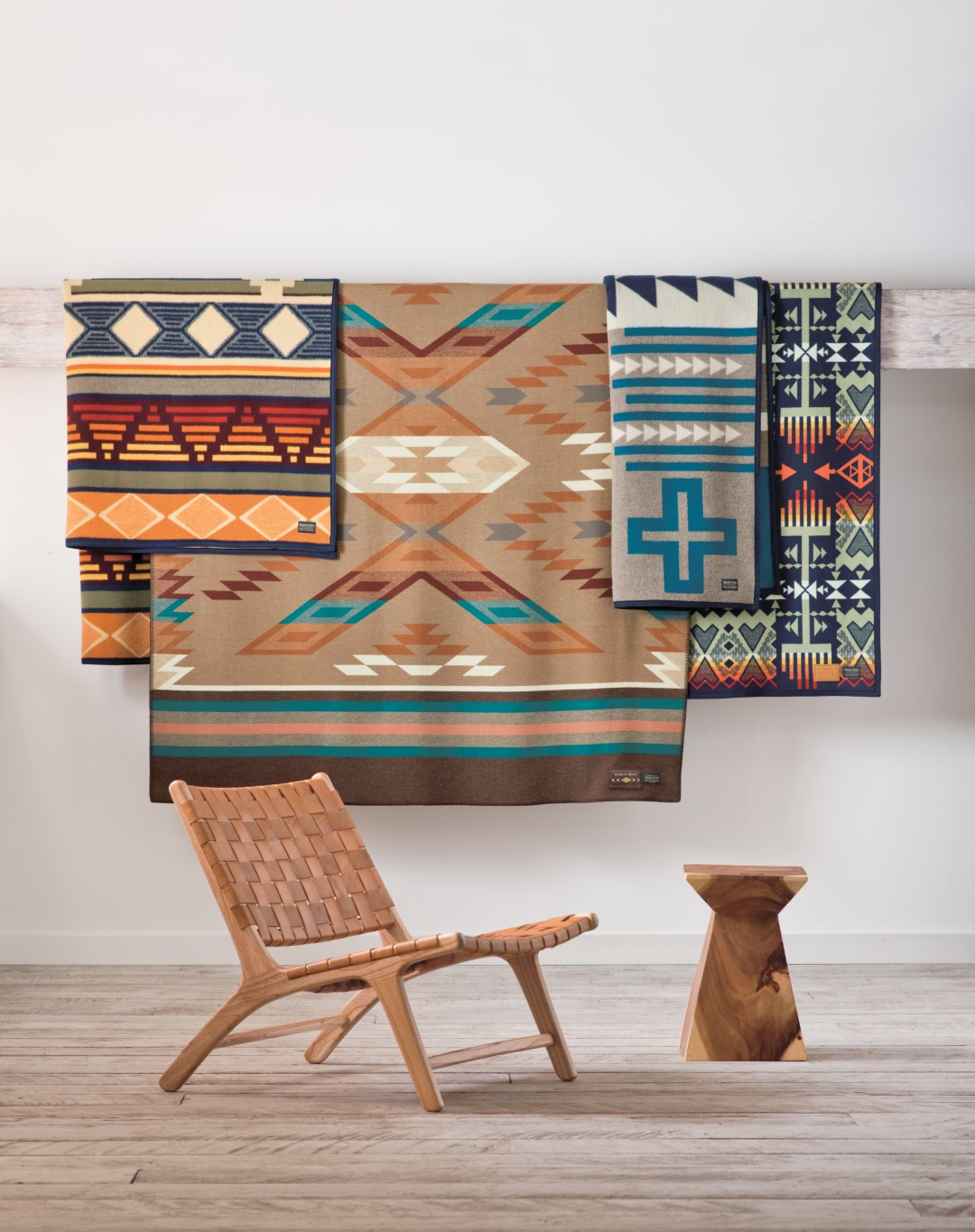 Patterned blankets hanging on wall with leather chair