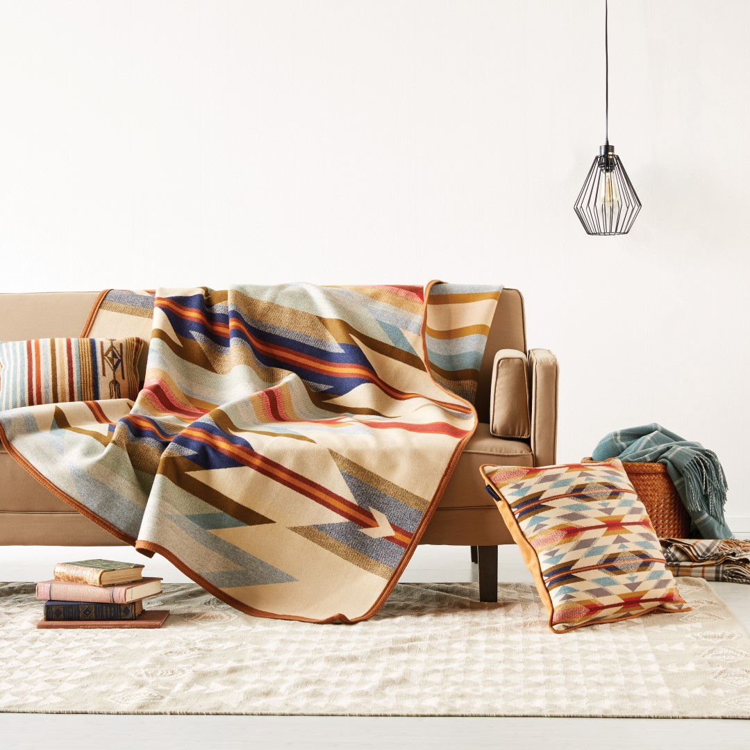 beige sofa covered in blankets